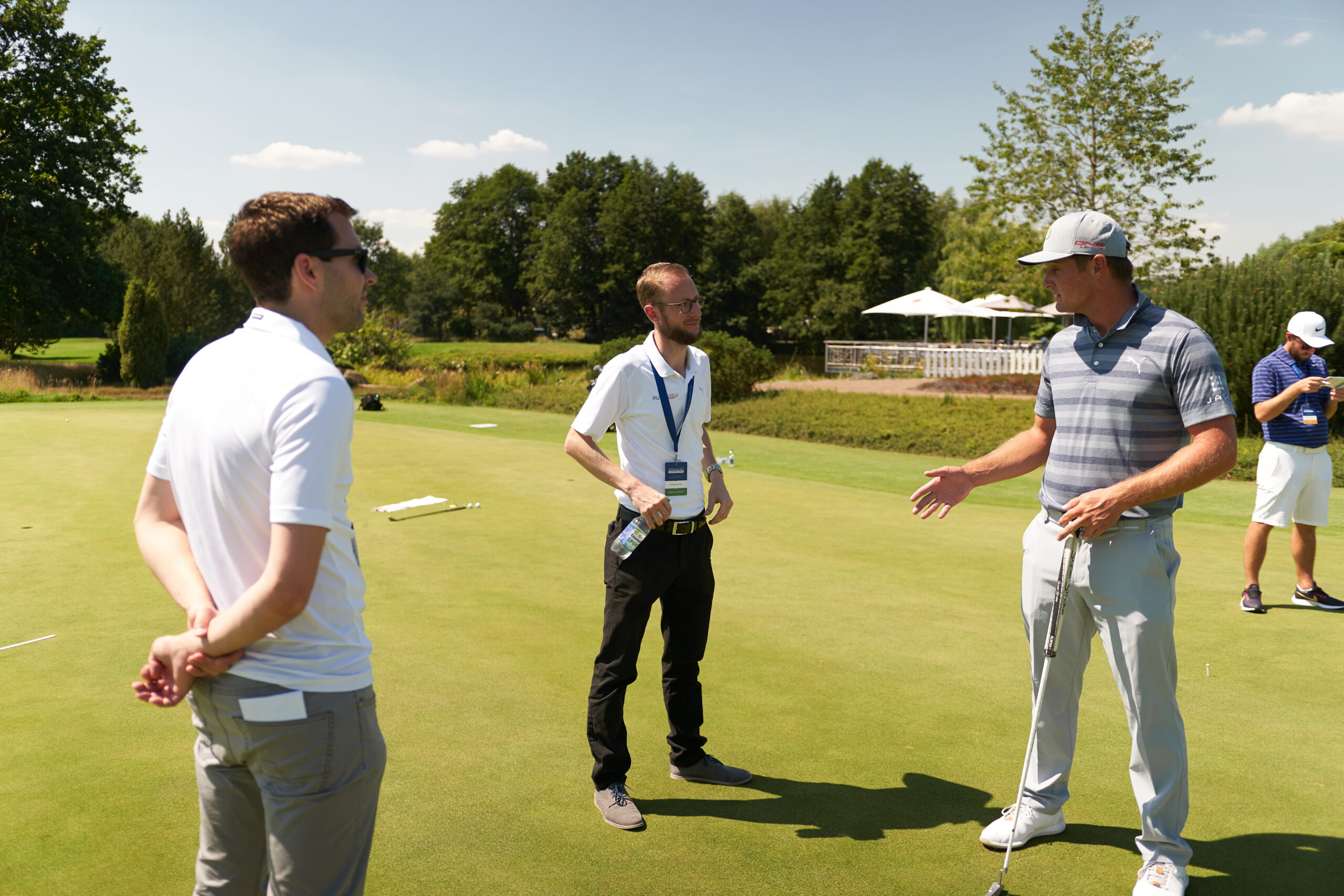 Bryson DeChambeau discusses details with Lukas (middle) and Christoph (right) during the Porsche European Open in Hamburg, where he was able to test PuttView Outdoor. © puttview.com